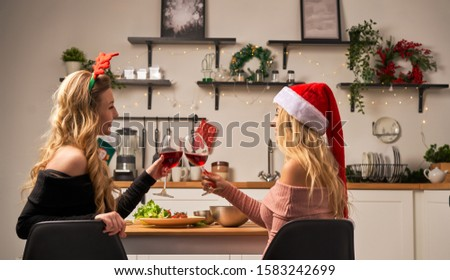 Two women sitting at festive table with wine glasses in kitchen at Christmas. #1583242699
