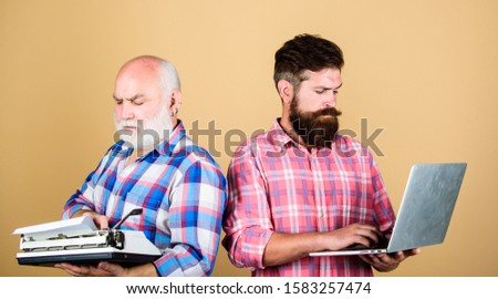 competitors. father and son. family generation. technology battle. Modern life. retro typewriter vs laptop. New technology. youth vs old age. business approach. two bearded men. Vintage typewriter. #1583257474