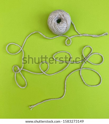 Ball of string on green background #1583273149