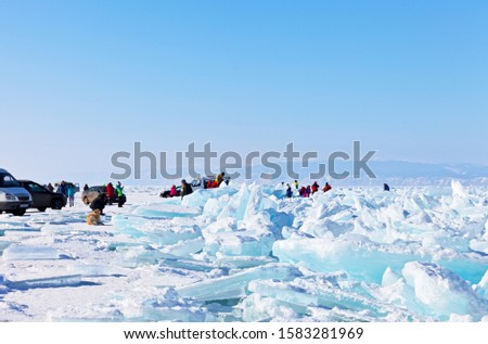 Winter Baikal Lake. Tourists arrived by cars on ice to take pictures of large beautiful blue ice hummocks (focus on ice, people out of focus)