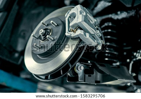 Disc brake of the vehicle for repair, in process of new tire replacement. Car brake repairing in garage.Suspension of car for maintenance brakes and shock absorber systems.Close up. Royalty-Free Stock Photo #1583295706