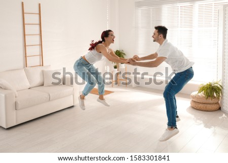 Beautiful young couple dancing in living room #1583301841