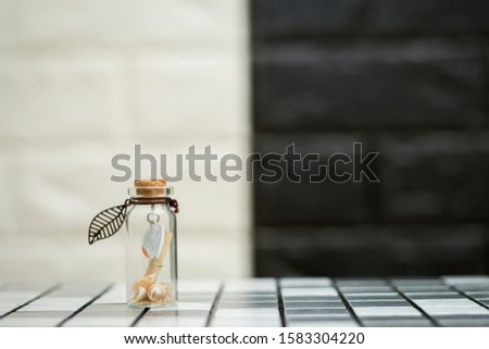 Sailboat and tiny shells in a tiny glass jar #1583304220