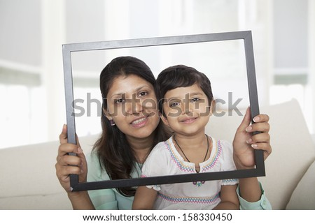 Mother and daughter looking through a picture frame  #158330450