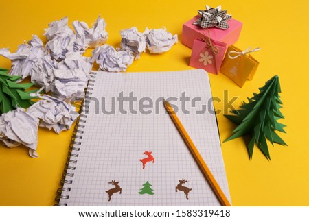 gift box and green origami trees with notepad on yellow desk, table #1583319418