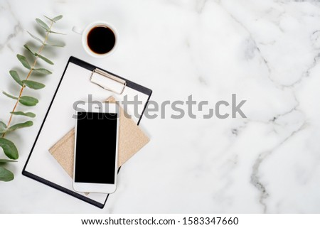 Flatlay business home office desk with office supplies and smartphone. Top view with copy space. Mobile phone, eucalyptus branch, clipboard, paper notebook and cup of coffee on marble table. #1583347660