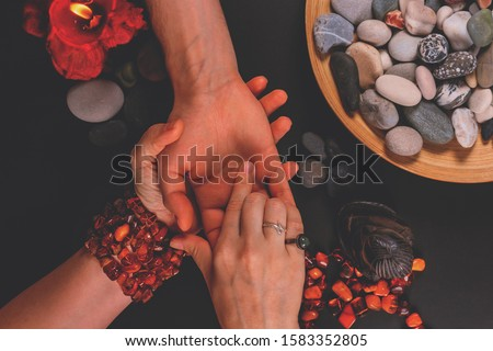 Young fortune teller divines the hand of young man around candles and other magical paraphernalia. Divine magic and occultism concept. Divination. Top view, toned. Royalty-Free Stock Photo #1583352805