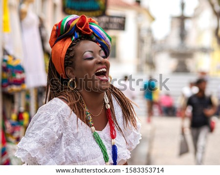 Happy Brazilian woman of African descent dressed in traditional Baiana costumes in the Historic Center of Salvador da Bahia, Brazil. #1583353714