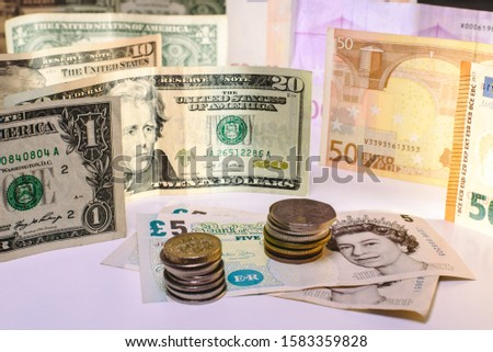 Pound sterling bill and English coins cornered by euros and dollars. #1583359828