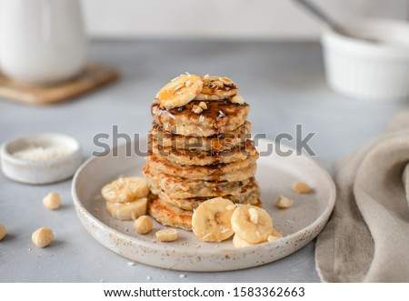 tasty oatmeal pancake with banana, nuts and date syrup. gray background, horizontal image Royalty-Free Stock Photo #1583362663