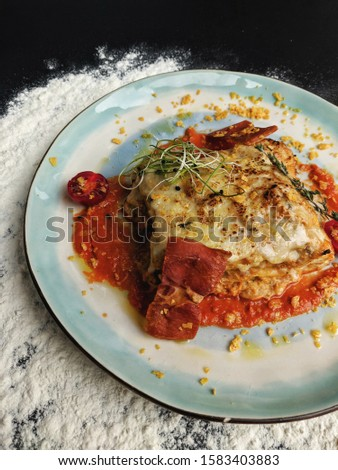 Delicious lasagna. Pasta on the plate. Colorful tasty picture. Lasagna with tomato sause and prosciutto chips.