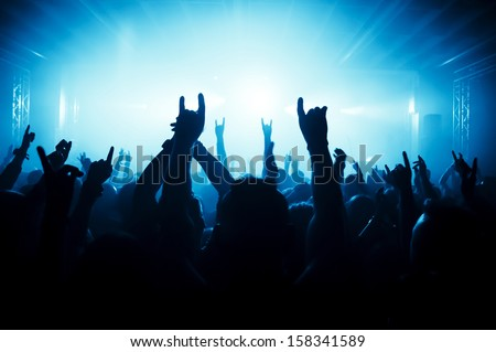 silhouettes of concert crowd in front of bright stage lights #158341589