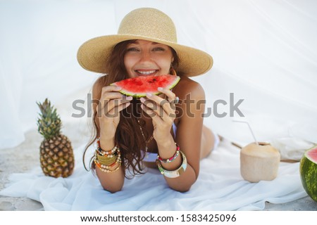 Beautiful woman holding watermelon and resting on the beach near the water. Tropical fruits diet concept. Summer holiday idyllic. Portrait of happy young slim mixed race Asian Caucasian girl in bikini