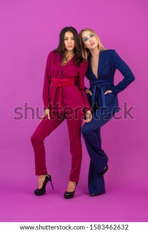 high fashion style two attractive women on violet background in stylish colorful evening suits of purple and blue color, friends having fun together, fashion trend #1583462632