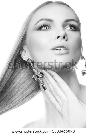 Beautiful fashion model woman portrait, perfect skin, blonde hair style, perfect skin, bright make-up, hand near neck, jewelry earrings. Black and white #1583465098
