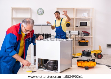 Two contractors repairing fridge at workshop #1583490361