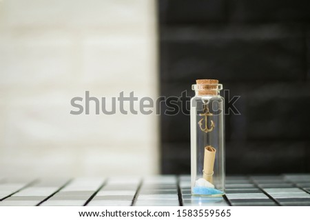 Tiny boat anchor and tiny shells in a tiny glass bottle #1583559565
