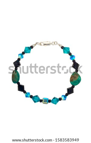 A mix of bicone, cube, irregular and seed beads in colors of blue, black, turquoise, and dichroic with silver findings make up this bead bracelet. Shown on a white background. #1583583949