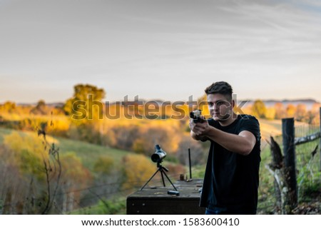 young caucasian man aiming pistol at target at outdoor firing range or shooting range in Kentucky #1583600410