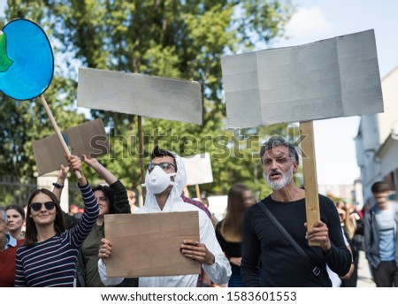 People with placards and protective suit on global strike for climate change. #1583601553