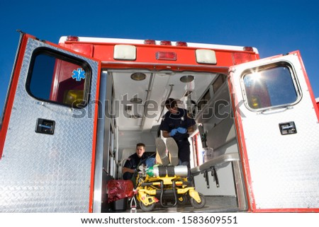 Paramedics with man on stretcher in ambulance, low angle view #1583609551