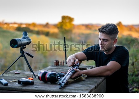 young caucasian man loading a rifle at outdoor firing range or shooting range in Kentucky #1583638900