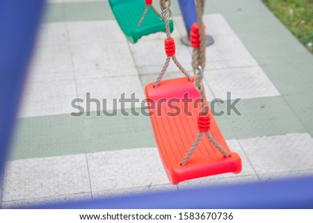Childs swing in a park .Plastic and Empty red and green  chain swings in children playground. chain swings hanging in garden #1583670736