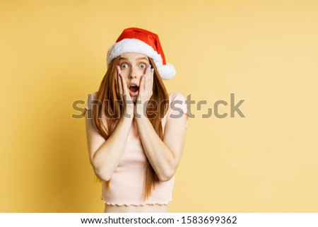 Emotive shocked caucasian redhead woman keeping both palms on cheeks, looking with amazement, wearing casual t yellow shirt, Santd hat, isolated on background. Christmas, emotions concept. #1583699362