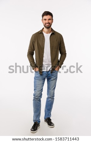 Full-length vertical shot carefree good-looking masculine bearded man in casual outfit, hold hands in jeans pockets and smiling, having friendly conversation, talking casually, white background #1583711443