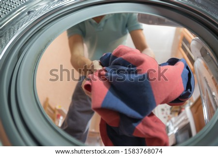 A man or woman throws dirty Laundry in the wash, look from the inside of the washing machine #1583768074