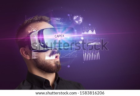 Businessman looking through Virtual Reality glasses with CAPEX inscription, new business concept #1583816206