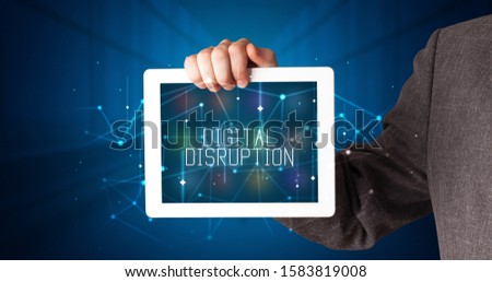 Young business person working on tablet and shows the digital sign: DIGITAL DISRUPTION #1583819008