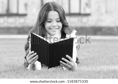 Who needs rest when theres another book to be read. Adorable small child read book on green grass. Cute little girl relax reading book outdoor. Seize every day with new book. School and knowledge. #1583875330