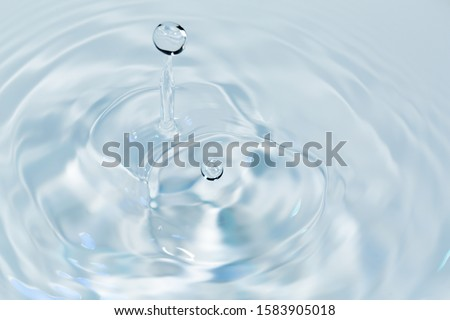 Water drops falling on water surface Royalty-Free Stock Photo #1583905018