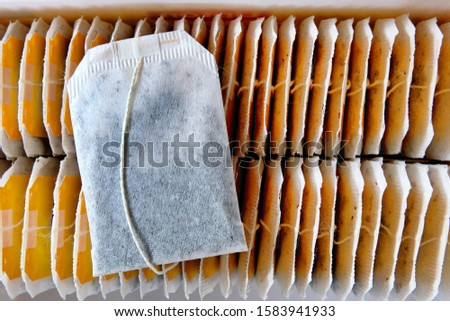 A tea bag lying on top of rows of other neatly arranged teabags inside a recently opened tea box. A choice selection of teabags for a morning drink and a refreshing afternoon break. #1583941933