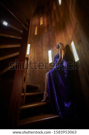 Artistic image of sexy blonde woman posing in rustic spiral stair case #1583953063