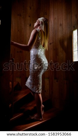 Artistic image of sexy blonde woman posing in rustic spiral stair case #1583953066