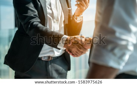 Two businessmen shaking hands together while sitting by windows.Mature businessman discuss information with a colleague in a modern business lounge high up in an office tower overlooking the city. #1583975626