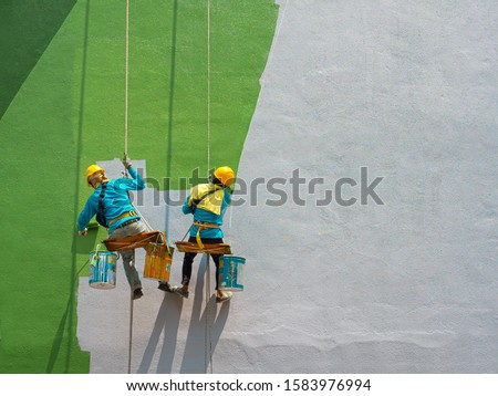 Two painters are painting the exterior of the building on a dangerous looking scaffolding hanging from a tall building with copy space. Royalty-Free Stock Photo #1583976994