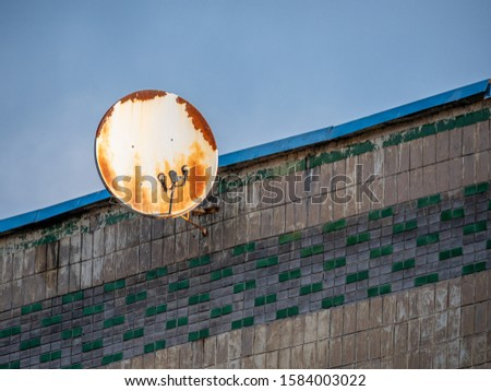 Round shape damaged rusty satellite antenna on grey building wall background and blue skies in above. Geometric variations and abandoned communications concept #1584003022
