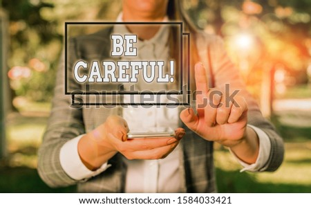 Handwriting text Be Careful. Concept meaning making sure of avoiding potential danger mishap or harm Woman in grey suites holds mobile phone. #1584033421