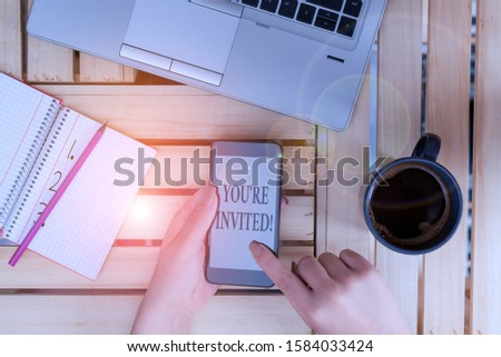 Writing note showing You Re Invited. Business photo showcasing make a polite friendly request to someone go somewhere woman with laptop smartphone and office supplies technology. #1584033424