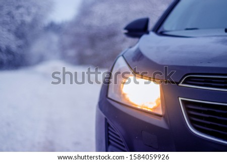 Car in winter in nature outside the city. Snow picture. Snow on the road. Winter road. The white trees. Black car. The car on the road.