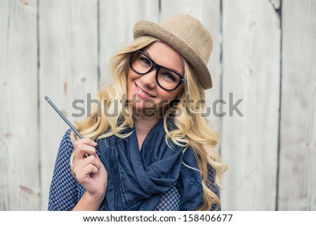 Smiling trendy blonde holding pencil on wooden background #158406677