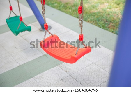 Childs swing in a park .Plastic and Empty red and green chain swings in children playground. chain swings hanging in garden #1584084796