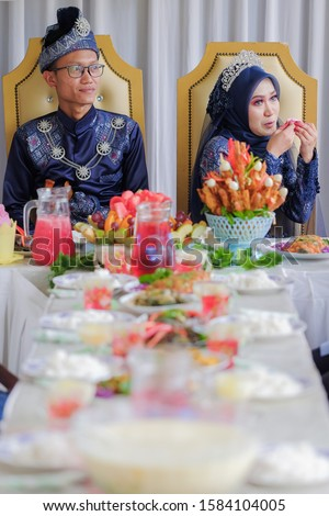 The bride couple  wearing Malay traditional  cloth  eats with their family or Makan Beradab  in wedding ceremony . Happy & Family Concept #1584104005