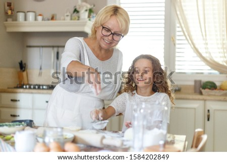 Happy senior woman with adorable granddaughter cooking together on kitchen, they feel good together. Horizontal view. #1584202849