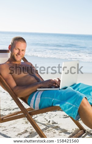 Handsome man on the beach using his laptop while sunbathing #158421560