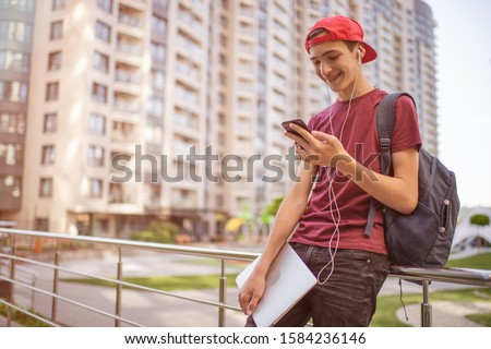 Smiling teenager  looks to the cell phone screen, in the city.  Young man stands with a smartphone, in the street.  Happy teenage boy is using mobile phone, outdoors. Soft focus effect. #1584236146