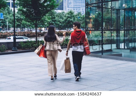 Back view of happy multiracial couple in casual clothes walking and talking with shopping bags and big present box after shopping on street  #1584240637